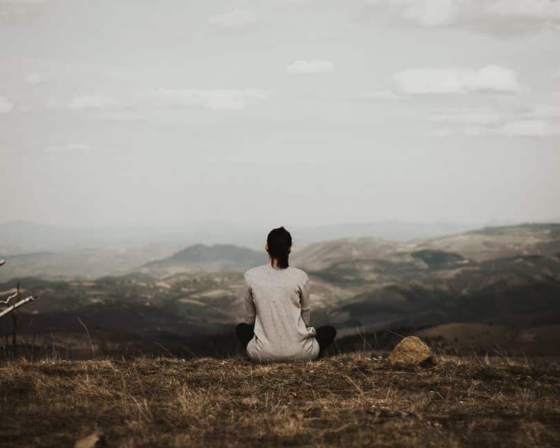 Mulher sozinha olhando para o horizonte