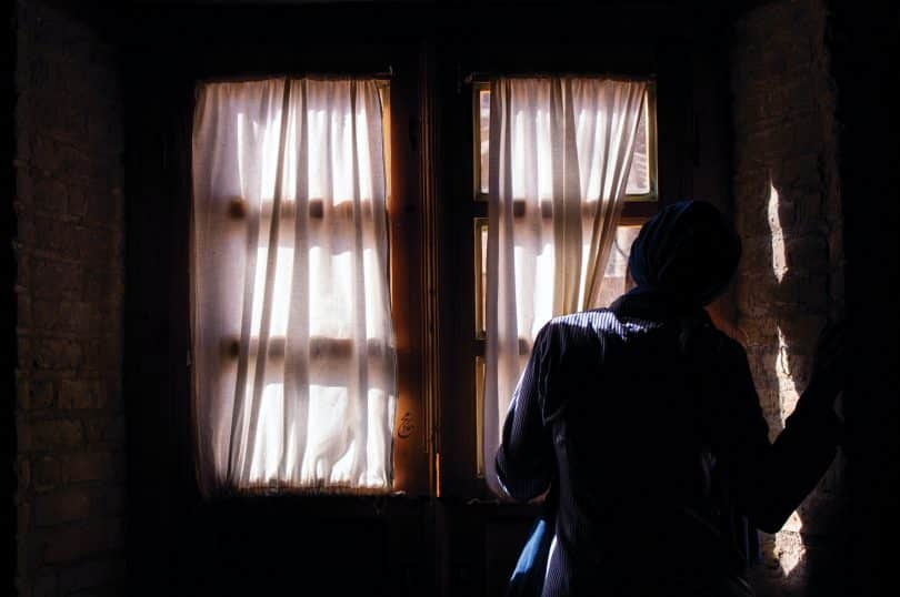 Mulher olhando para a janela segurando a cortina