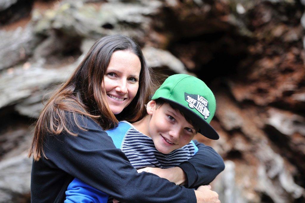 Mulher abraçando menino por trás, e os dois sorrindo para a câmera.