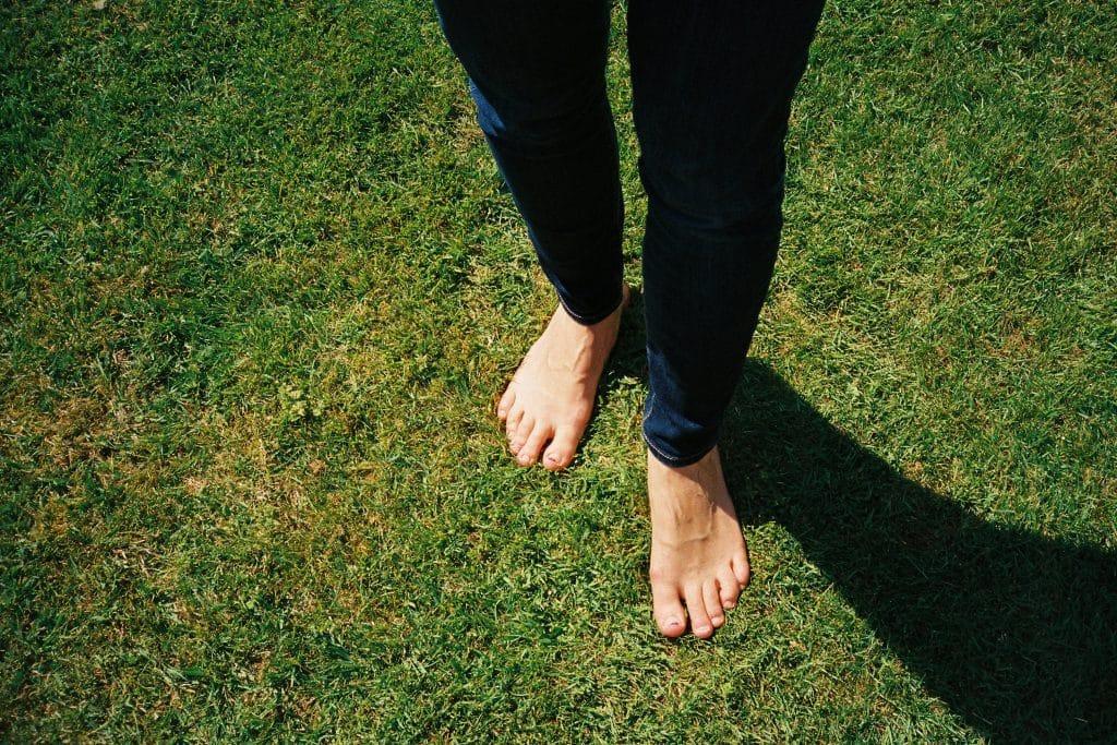 Pessoa com pés descalços em um gramado