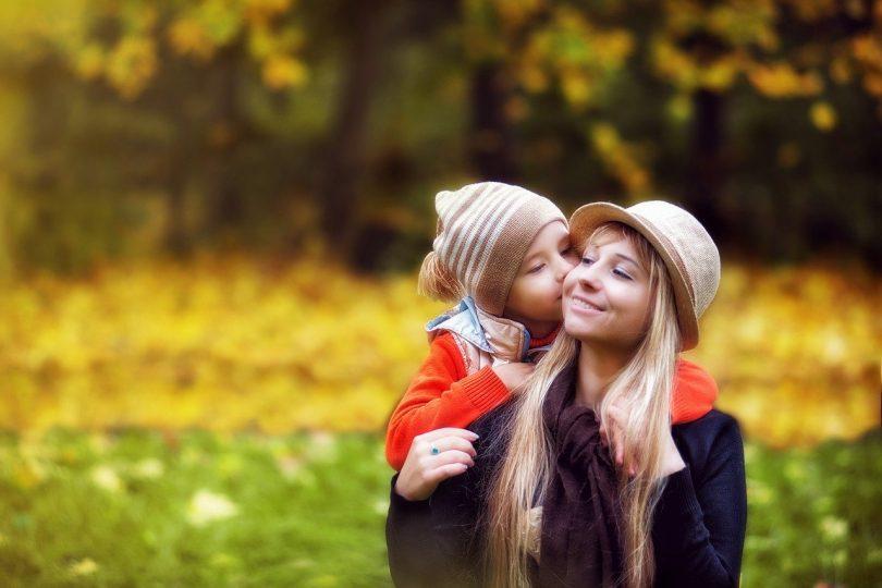 Menino beijando bochecha de mulher, que está abaixada para os dois ficarem da mesma altura.