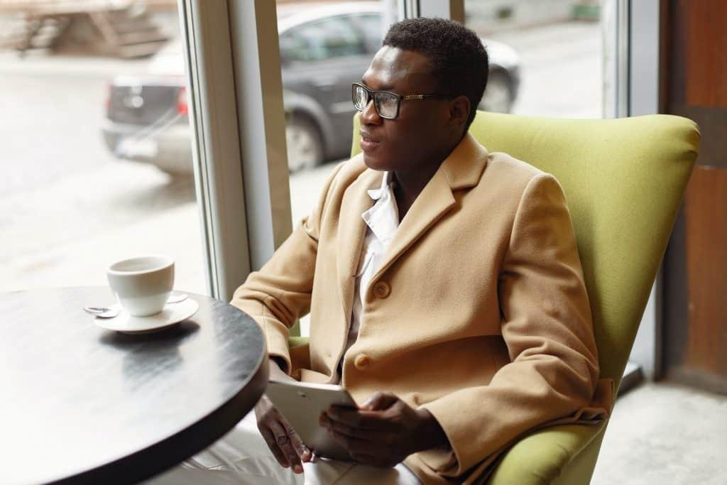 Homem usando um casaco de frio, pensativo, olhando pela janela em uma mesa de um café.