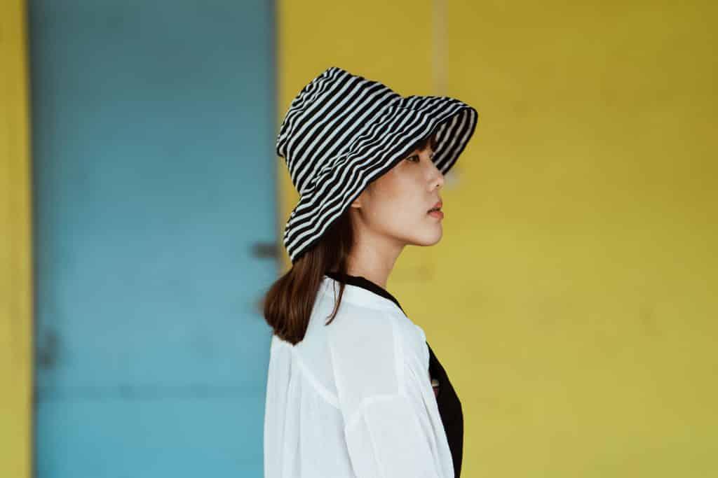 Mulher de chapéu e traços sino-asiáticos vista de perfil.