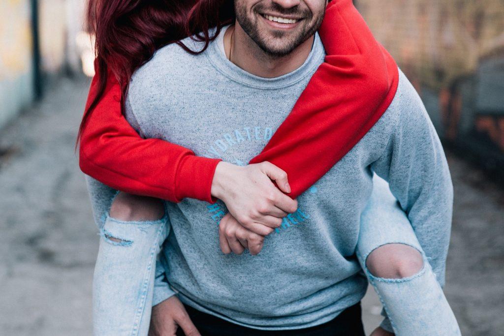 Imagem de um casal jovem. Ele carrega a moça em suas costas. Estão felizes. A imagem retrata a questão da relação entre o casal e o orgasmo feminino.
