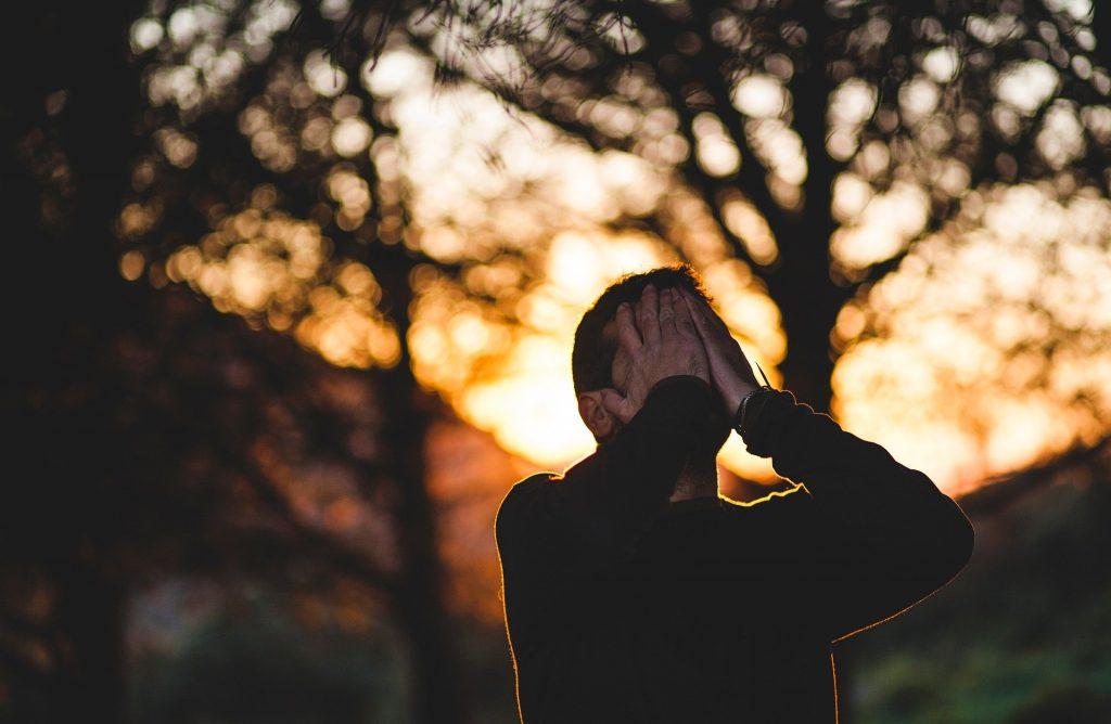 Imagem de um homem em meio a uma floresta em pleno por do Sol. Ele está triste e decepcionado. Cobre o rosto com as duas mãos.