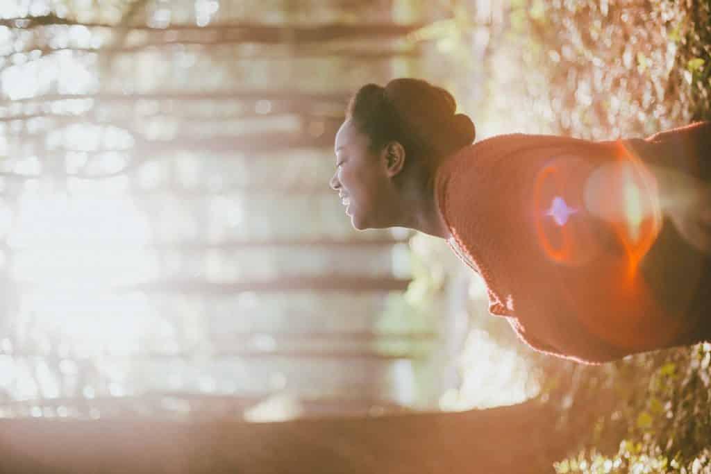 Imagem de uma mulher negra em uma floresta. Ela está ajoelhada e fazendo a oração do perdão.