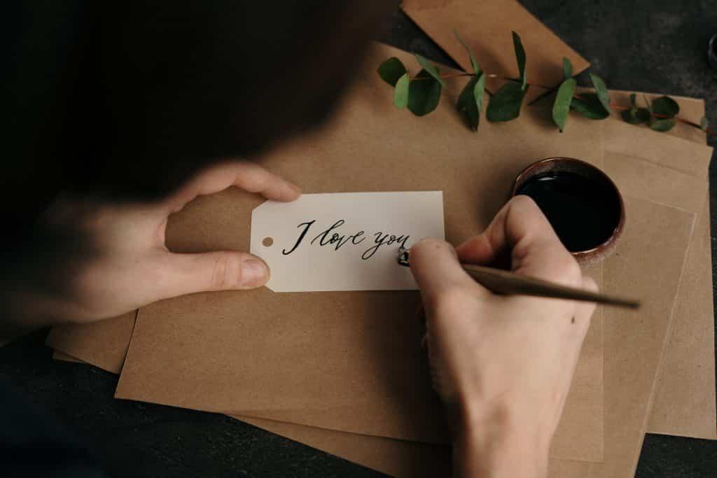 """Pessoa escrevendo as palavras """"eu te amo"""" em inglês em uma etiqueta com uma caneta à tinta."""