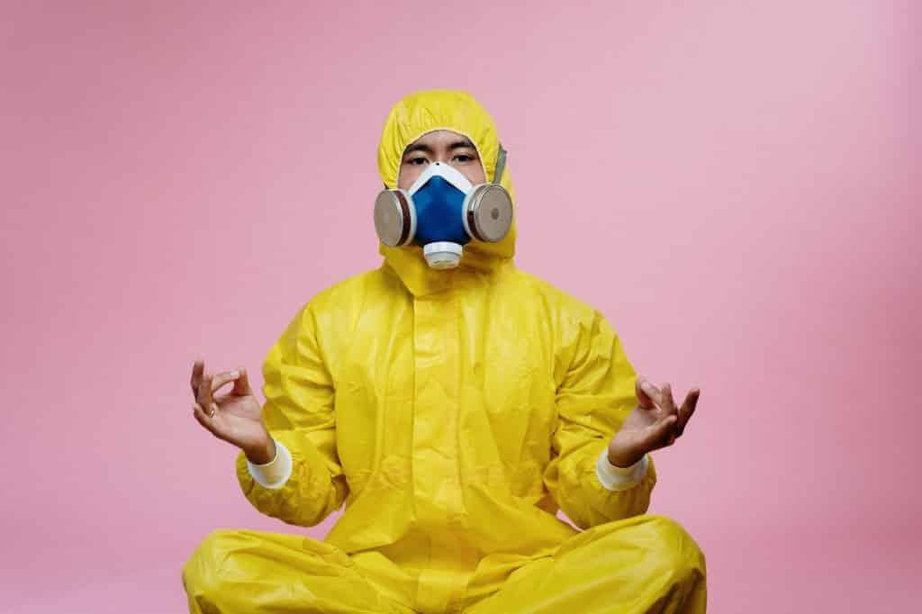 Homem com roupa e máscara de isolamento, sentado com as pernas cruzadas, meditando.
