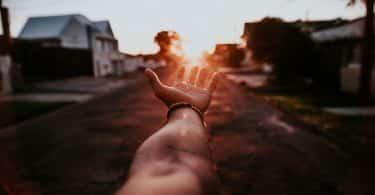 Braço esticado em direção a luz do sol, se pondo no horizonte.