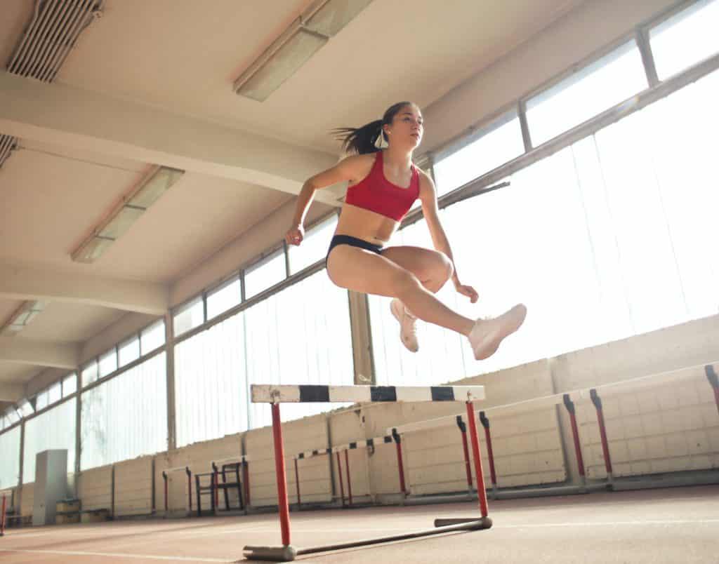 Mulher atleta pulando um obstáculo.