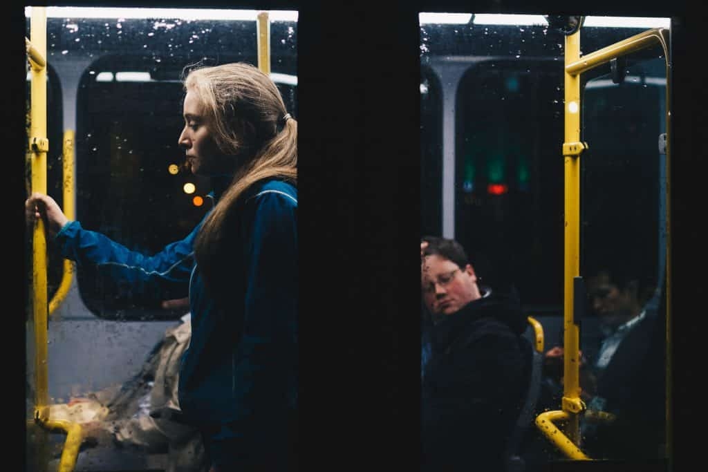 Mulher em pé vista da janela de um ônibus à noite.