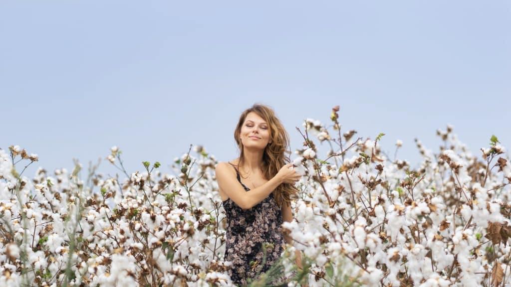 Mulher em pé em meio a um campo de flores, sorrindo.