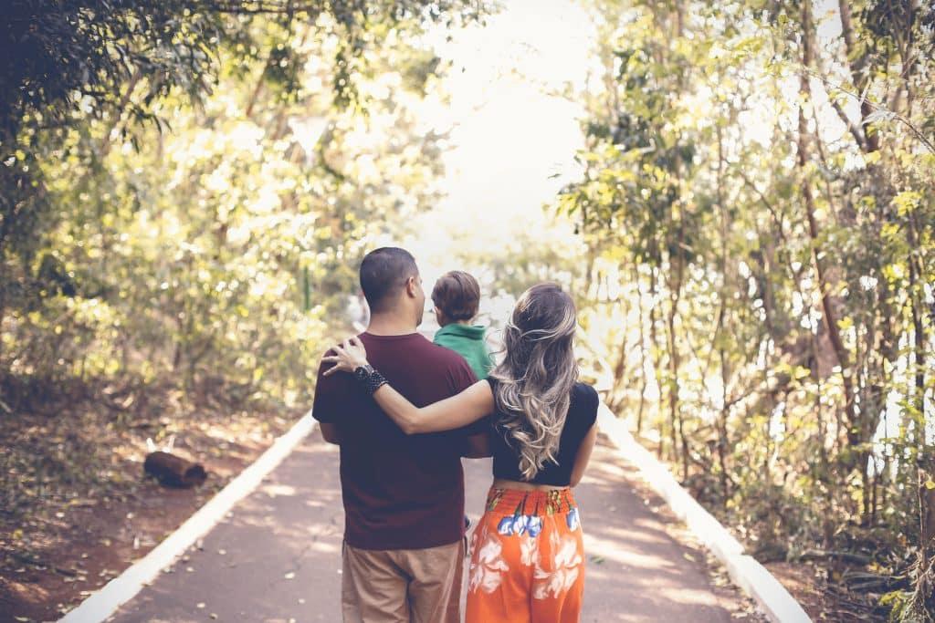 Mãe, pai e criança caminhando por um parque, vistos de costas.