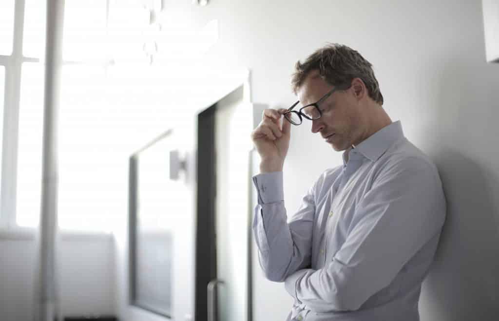 Homem com roupas sociais encostado na parede, com expressão séria, retirando os óculos do rosto.