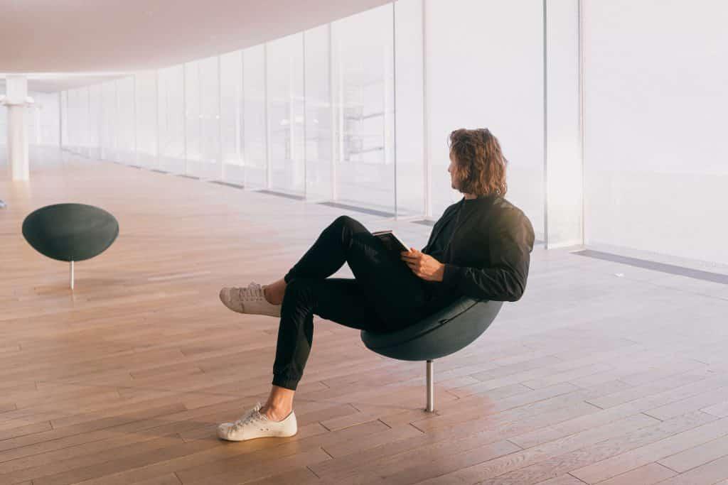 Homem sentado em uma cadeira, em um cômodo amplo e vazio, segurando um livro.