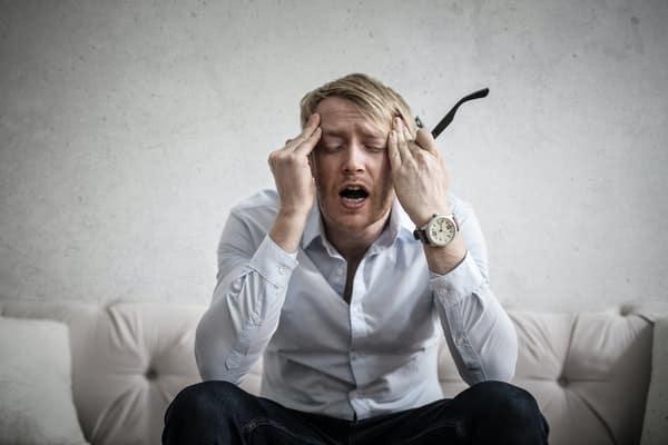 Homem sentado no sofá com expressão de estress