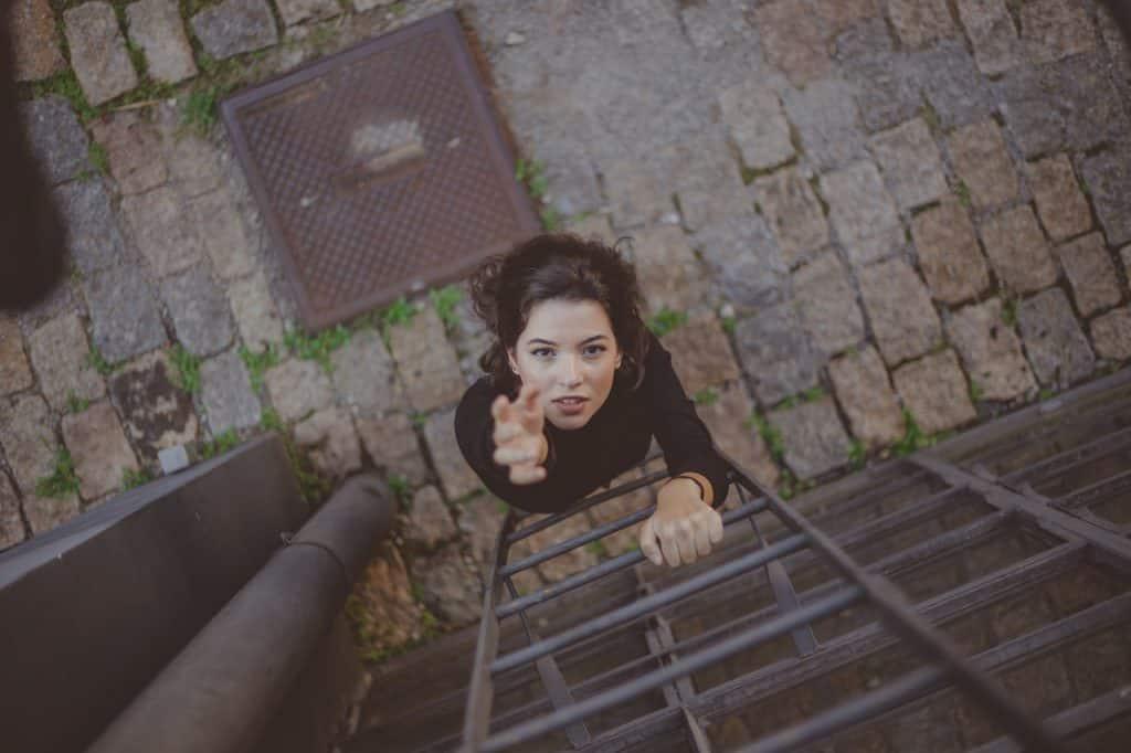 Mulher subindo escada de emergência, com uma mão esticada, tentando alcançar mais alto.