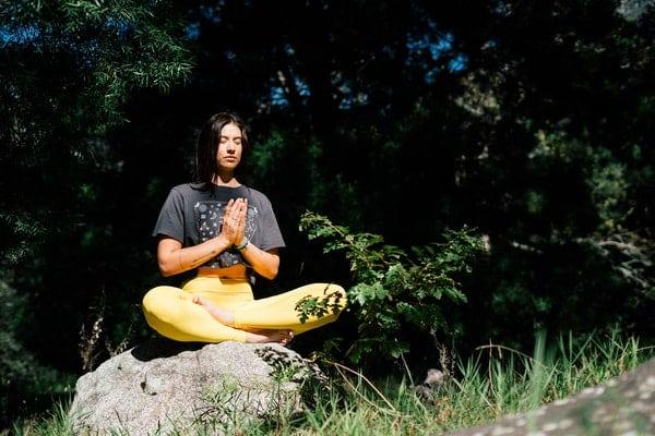 Mulher sentada em uma rocha meditando