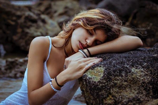 Mulher apoiada na pedra de olhos fechados