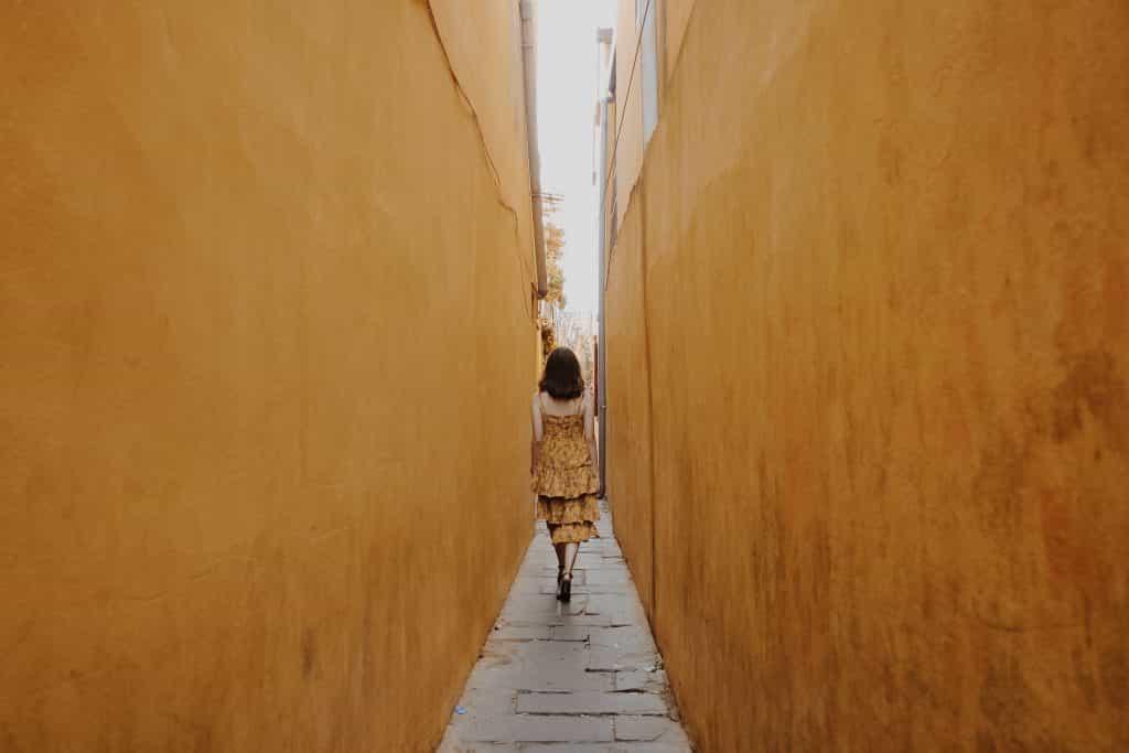 Mulher de vestido caminhando por um corredor estreito, vista de costas.