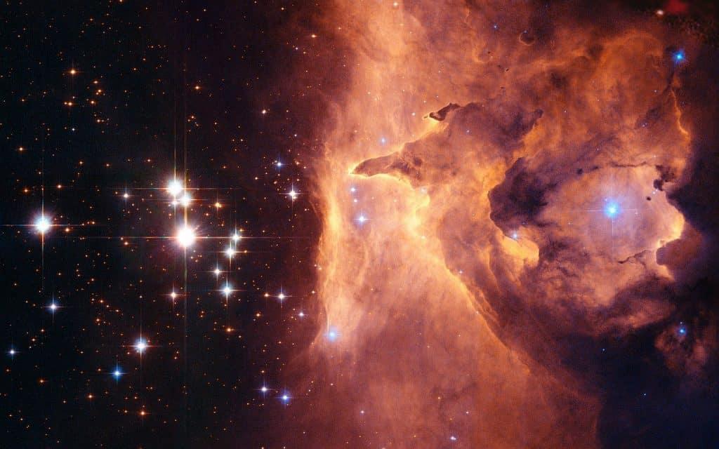 Imagem do universo estrelado e a quinta dimensão e ao lado de uma das estrelas uma mancha alaranjada representando o fogo.