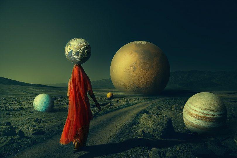 Imagem de uma mulher caminhando e segurando sobre a cabeça um planeta. Ao fundo da imagem e ao lado, vários planetas. A imagem retrata a transição planetária.