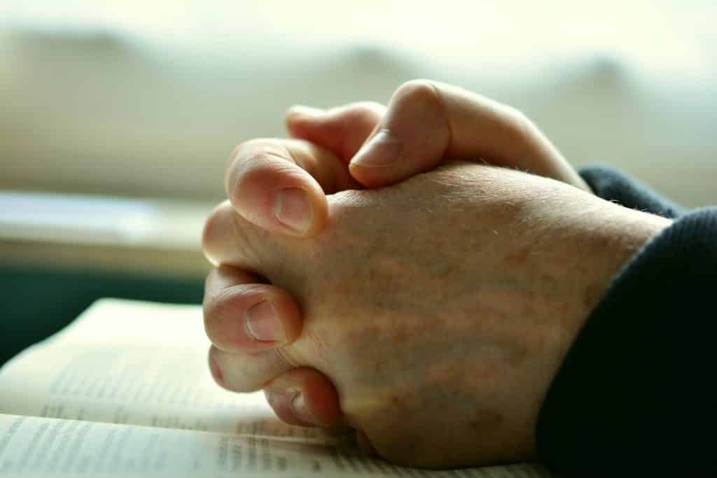 Imagem de mãos juntas em sinal de oração. As mãos estão sobre a bíblia em sinal da oração do perdão.