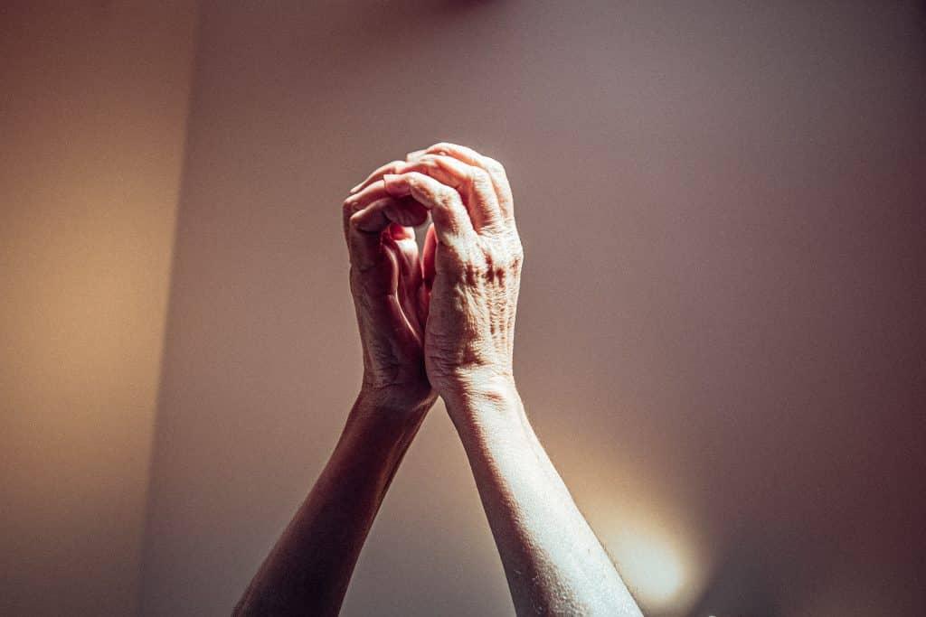 Mãos de uma pessoa com as palmas unidas para cima, em sinal de oração.