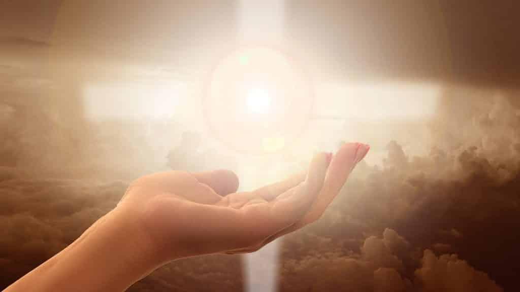 Imagem de uma mão e ao fundo uma cruz sendo iluminada. A cruz também está representando a espiritualidade das pessoas.