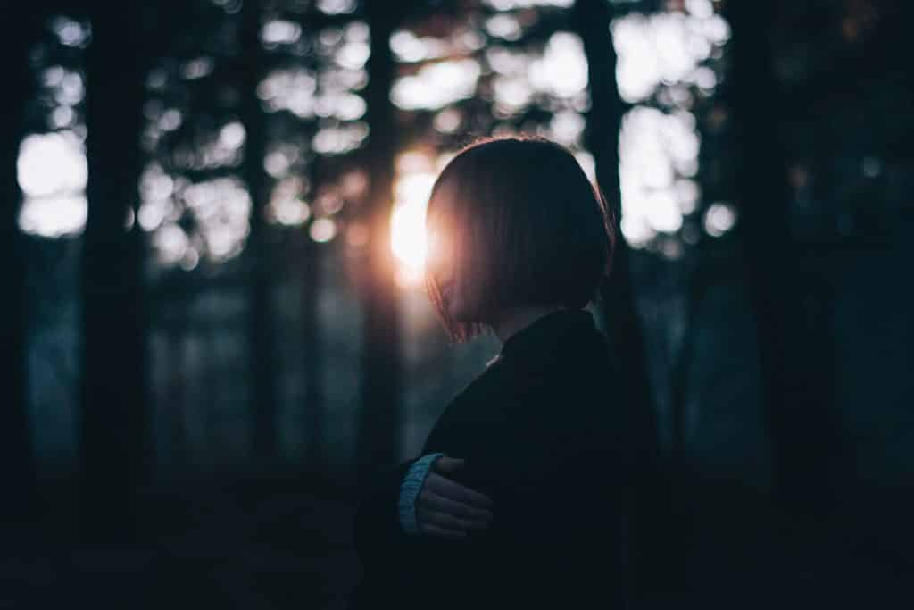 Mulher em um jardim olhando para frente com tristeza