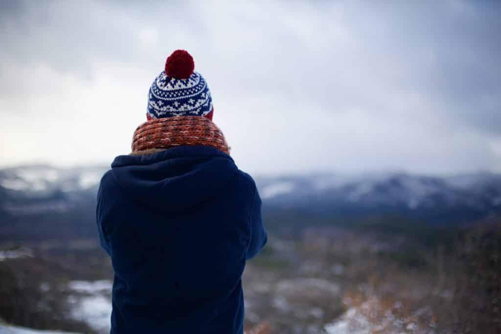 Pessoa usando roupas de frio e olhando para as montanhas