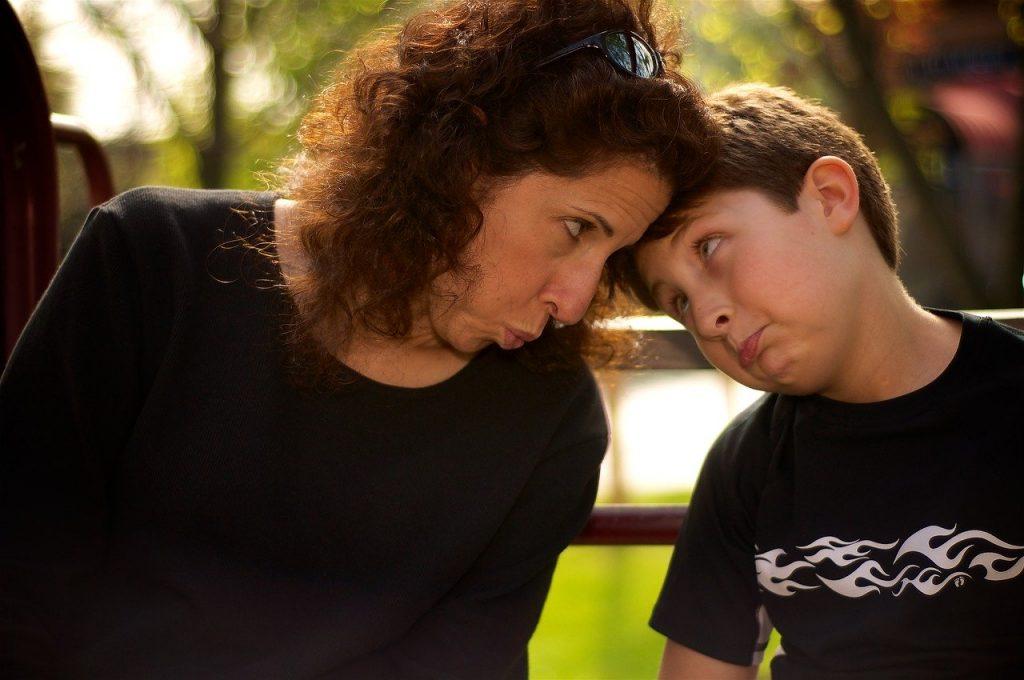 Mulher e menino sentados lado a lado, encostando suas testas e fazendo caretas.