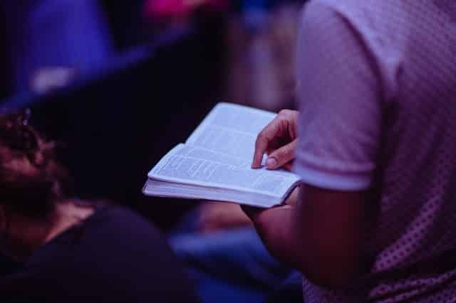 Homem lendo a bíblia em missa