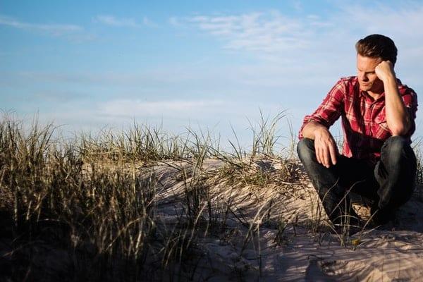 Homem pensativo sentado em areia com mato e céu azul ao fundo
