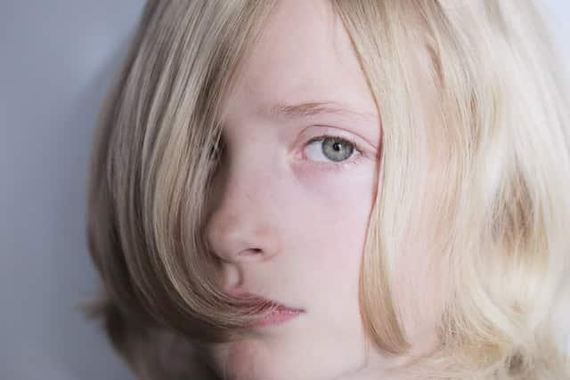 Rosto de criança com expressão vazia vista de perto com cabelos soltos