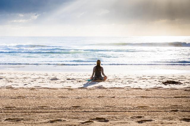 Mulher sentada na praia de costas com mar ao fundo em posição de lótus