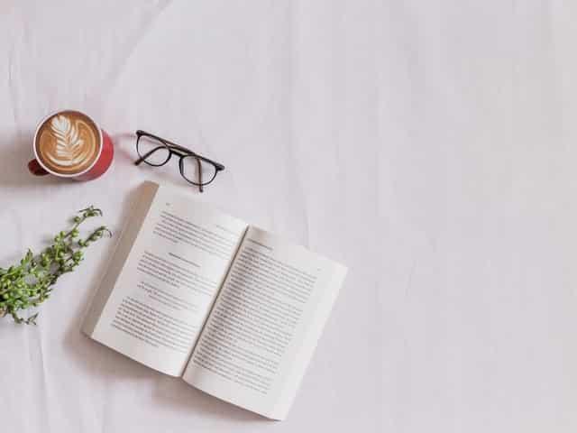 Livros aberto em cama com óculos e xícara de café ao lado