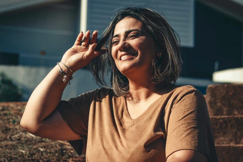 Mulher sorrindo enquanto mexe em seu cabelo.