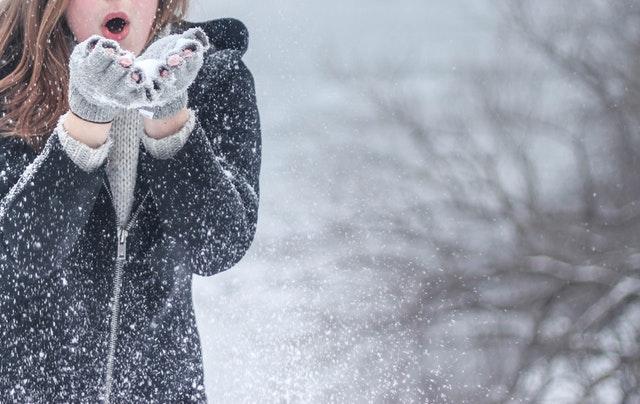 Mulher assoprando flocos de neve