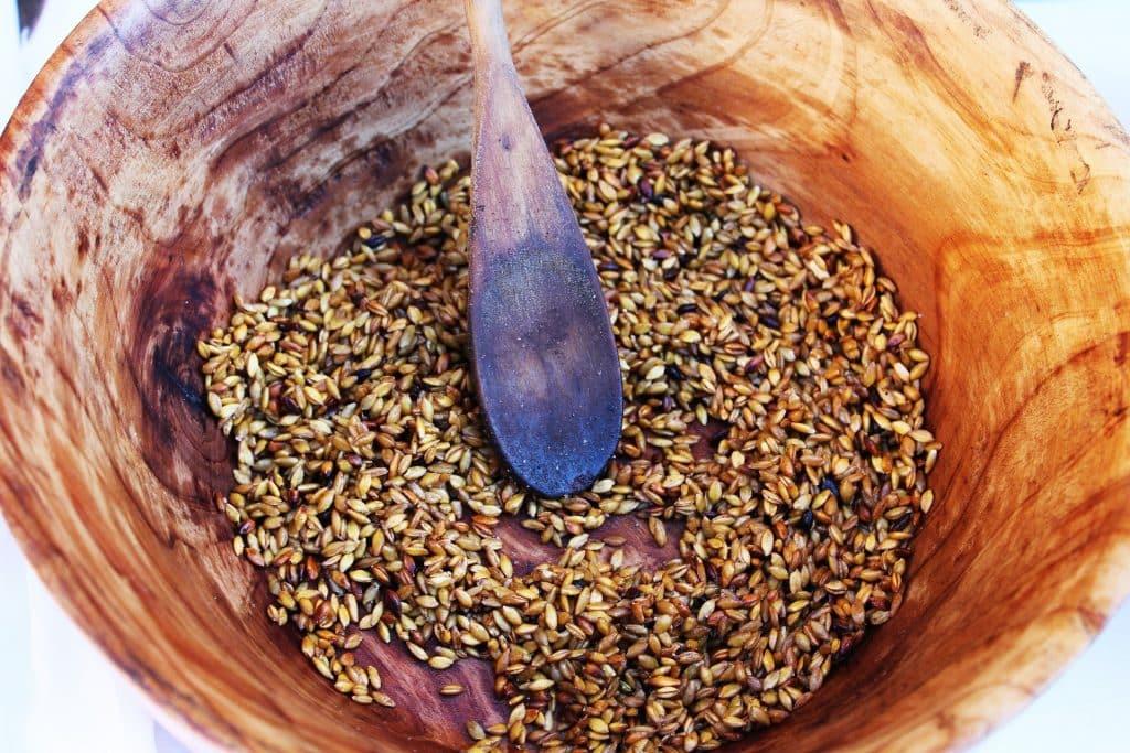 Imagem de um bowl de madeira com sementes de cereais.