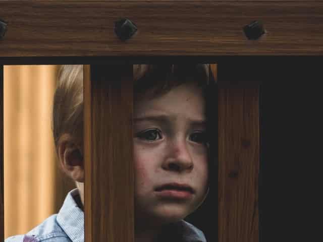 Garoto com expressão triste atrás de cerca de madeira