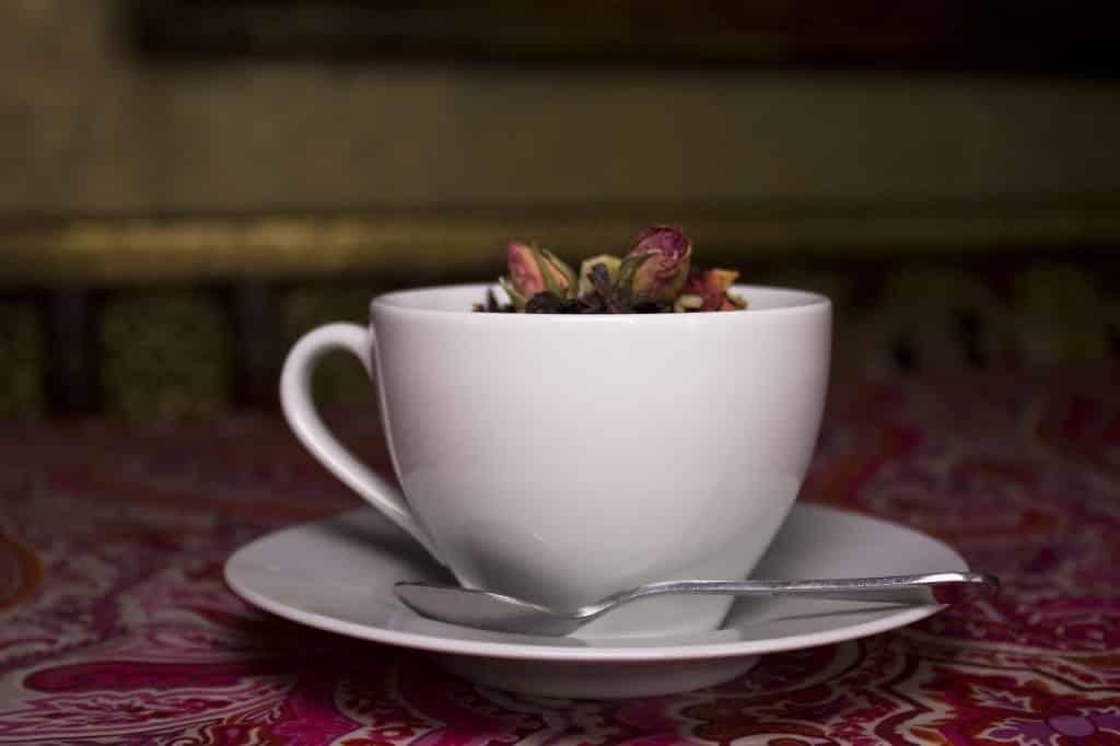 Imagem de chá para dor de estômago e fígado sendo servido em uma xícara branca com pires e uma colher.
