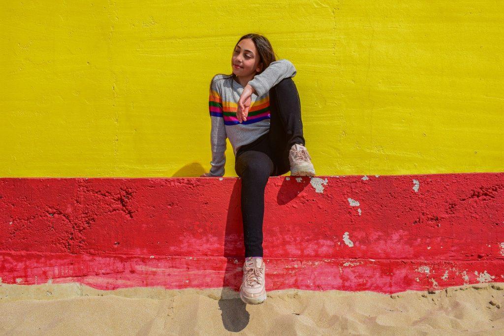 Imagem com fundo de uma parede pintada nas cores amarela e vermelha. À frente uma jovem, bem despreocupada, sentada e alegre.
