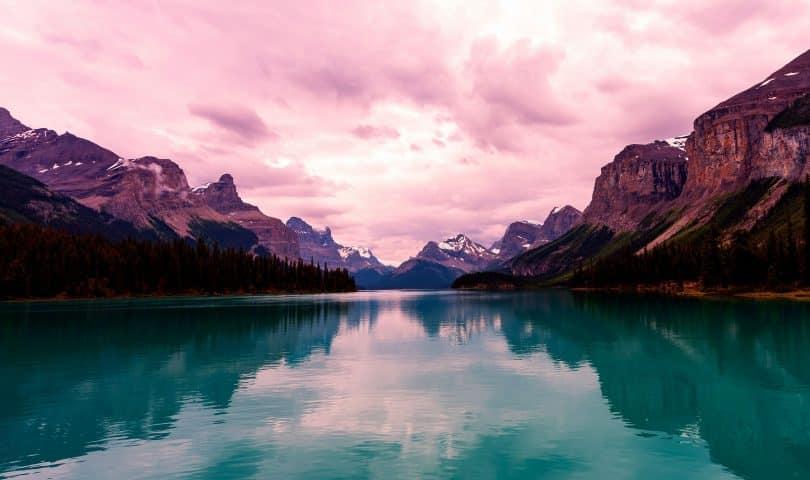 Paisagem de montanhas e um rio atravessando ao meio com céu nublado