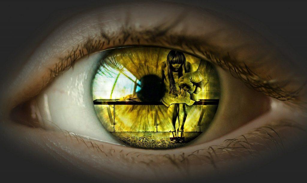 Imagem de um olho e ao fundo dele a imagem de uma mulher sentada com a cabeça baixa e a mão fechada de um homem pronto para agredí-la.