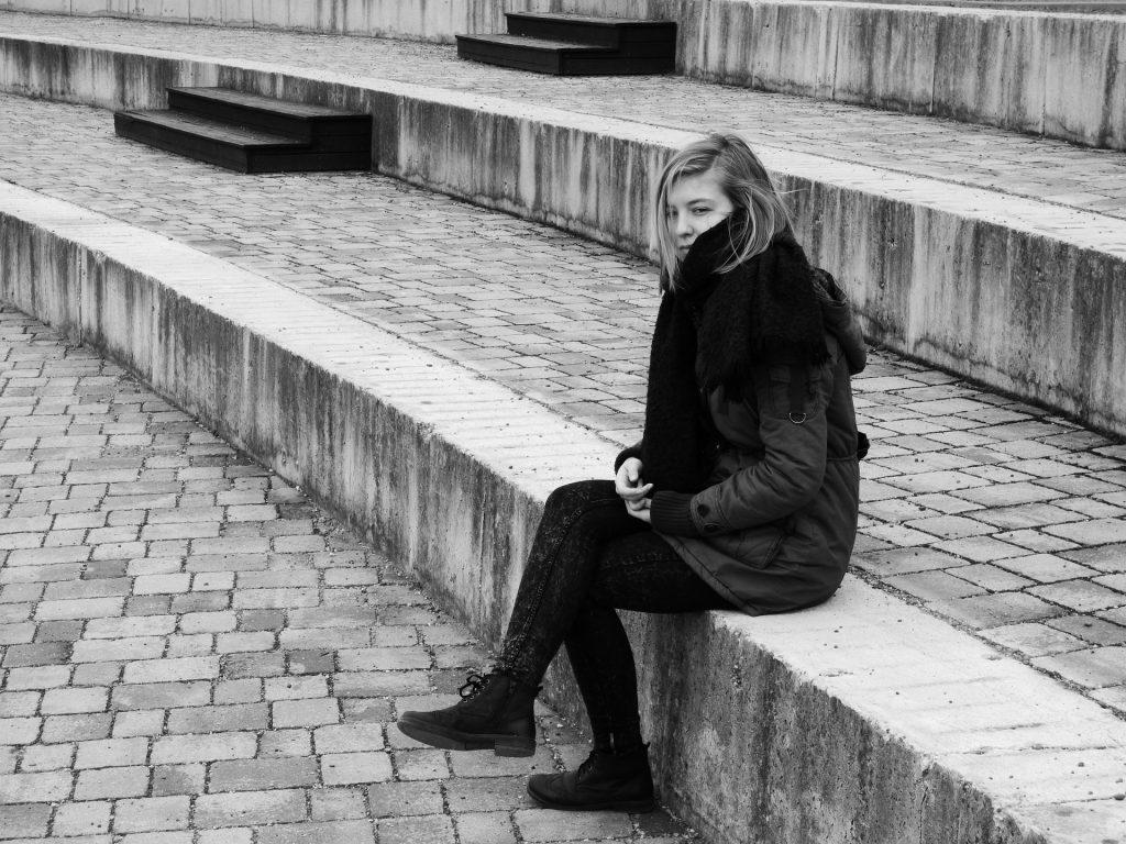 Imagem preto e branco de uma escadaria e uma mulher vestindo um look de inverno. Ela está sentada em um dos degraus da escadaria e parece estar muito triste e deprimida.