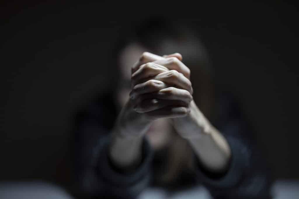 Imagem da silhueta de uma mulher que está sentada, com os braços esticados e com as mãos dadas. Ela parece estar triste e depressiva.