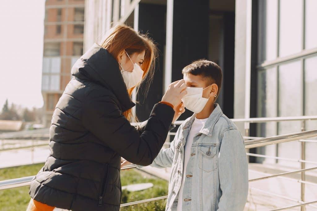 Mãe ajustando a máscara de proteção de seu filho, que está parado a sua frente.