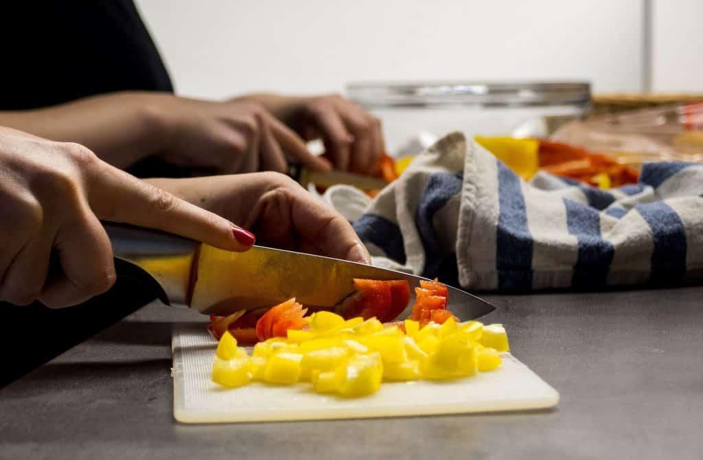Imagem das mãos de uma mulher na cozinha. Ela está picando legumes sobre uma tábua branca.