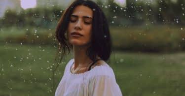 Mulher de olhos fechados em ambiente aberto, sob a chuva.